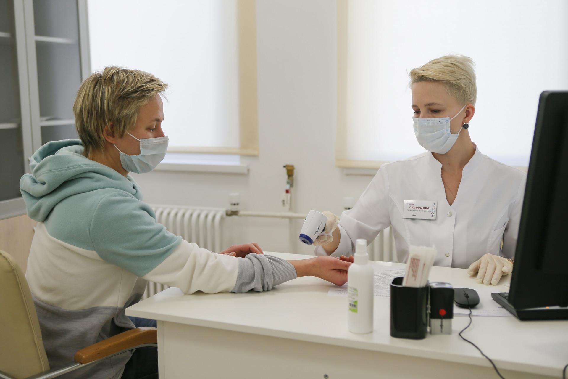 Petugas memeriksa suhu tubuh seorang wanita yang hendak menerima suntikan vaksin COVID-19 di Moskow, Sabtu (5/12)