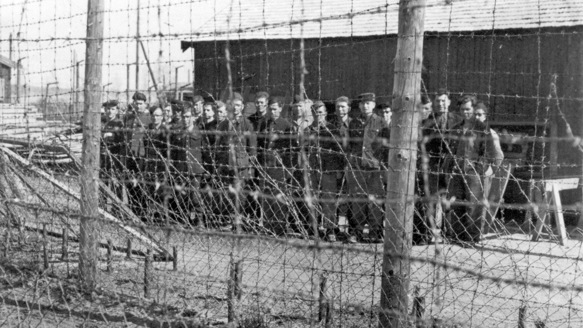 Prisioneiros de guerra soviéticos atrás de arame farpado no campo de Falstad