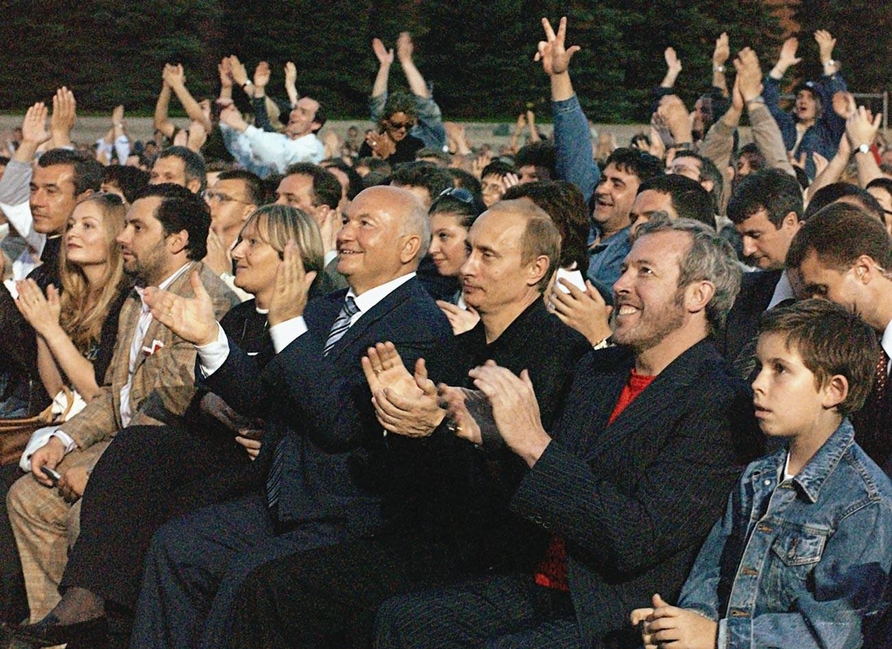 Руският президент Владимир Путин (в средата), кметът на Москва Юрий Лужков (вляво) и известният руски музикант Андрей Макаревич (вдясно) по време на концерт на легендарния певец и композитор.