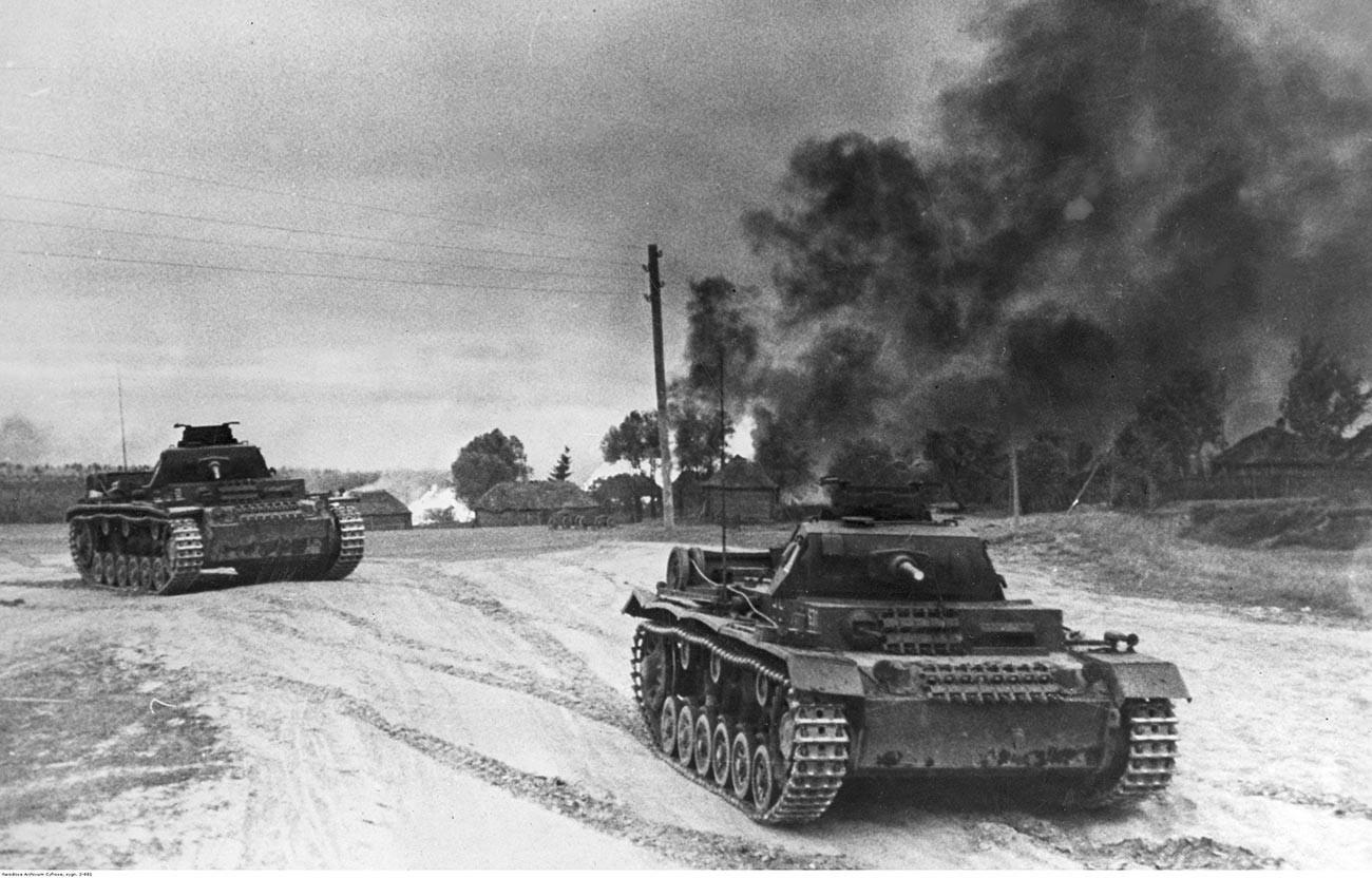 Германски тенкови PzKpfw III Ausf G со топови KwK 42 со калибар од 50 милиметри минуваат низ село во плам во околината на Москва.