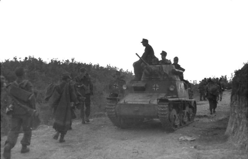 Soldados alemanes en marcha, tanque italiano Carro armato L.6/40 con insignia alemana.
