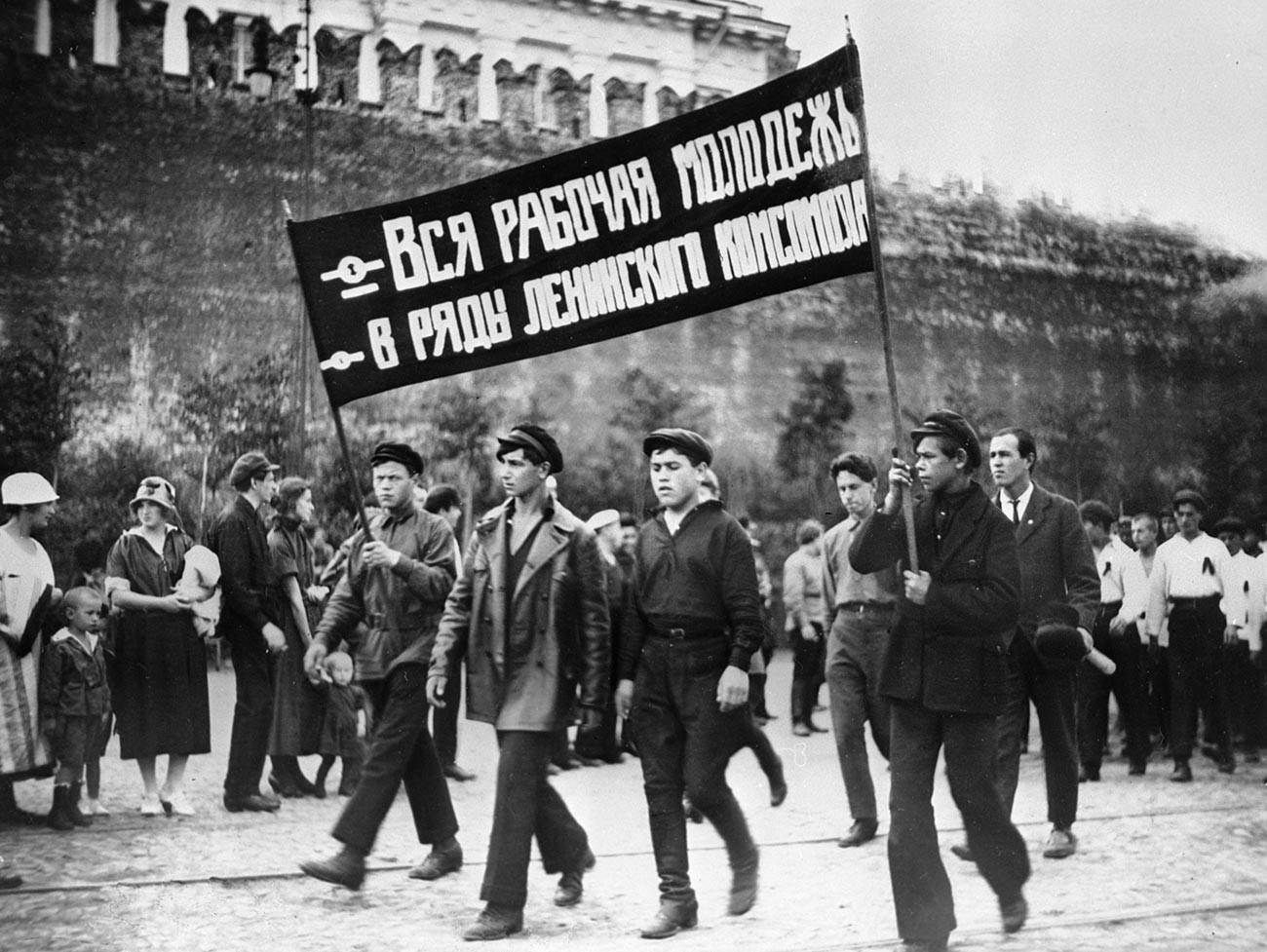 """Колона комсомолаца са паролом """"Сва радничка омладина – у редове Лењиновог комсомола"""" током демонстрације на Црвеном тргу."""