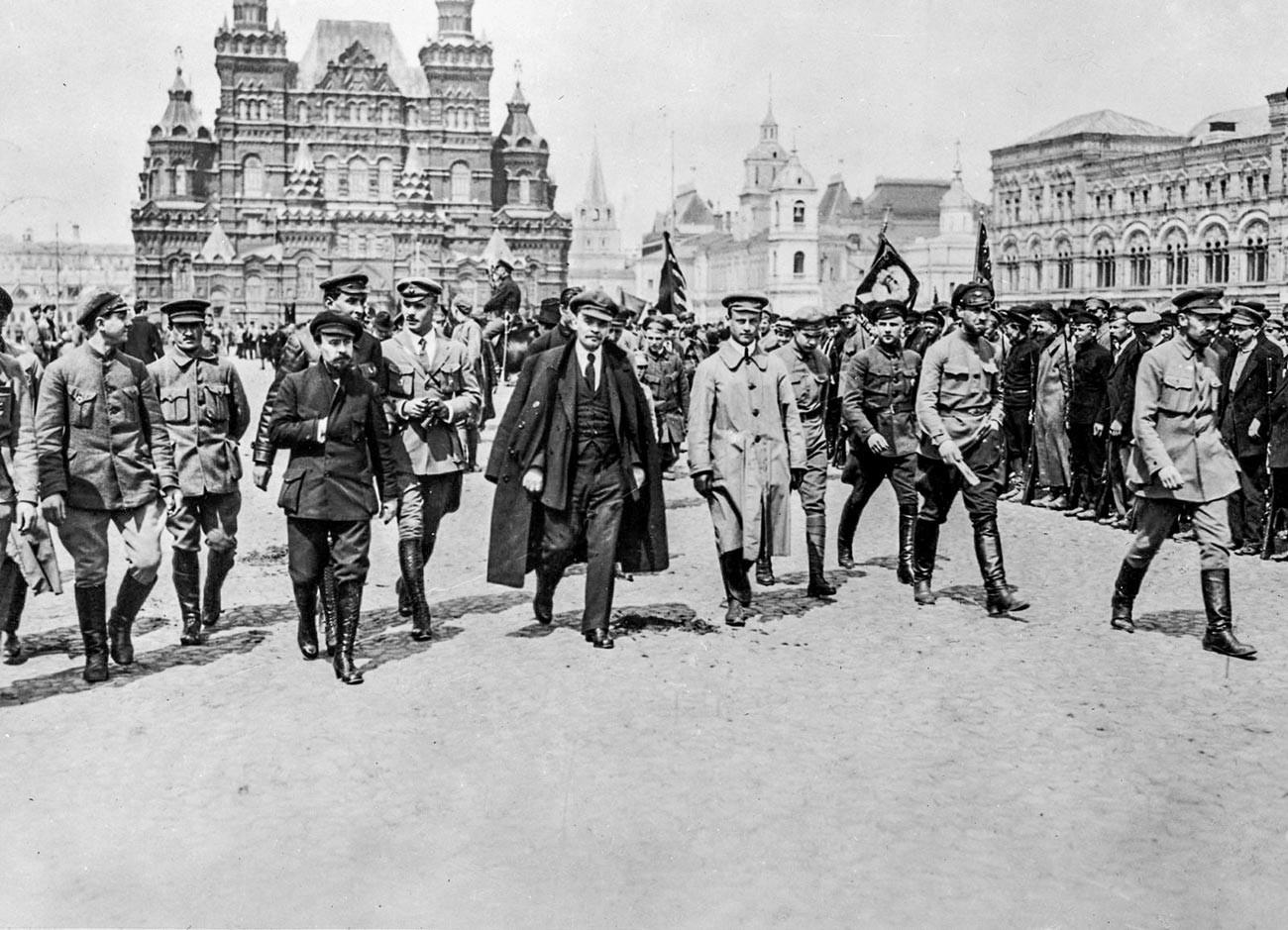 Pmimpin revolusioner proletariat Soviet Vladimir Lenin (tengah), berjalan bersama sekelompok komandan di Lapangan Merah.