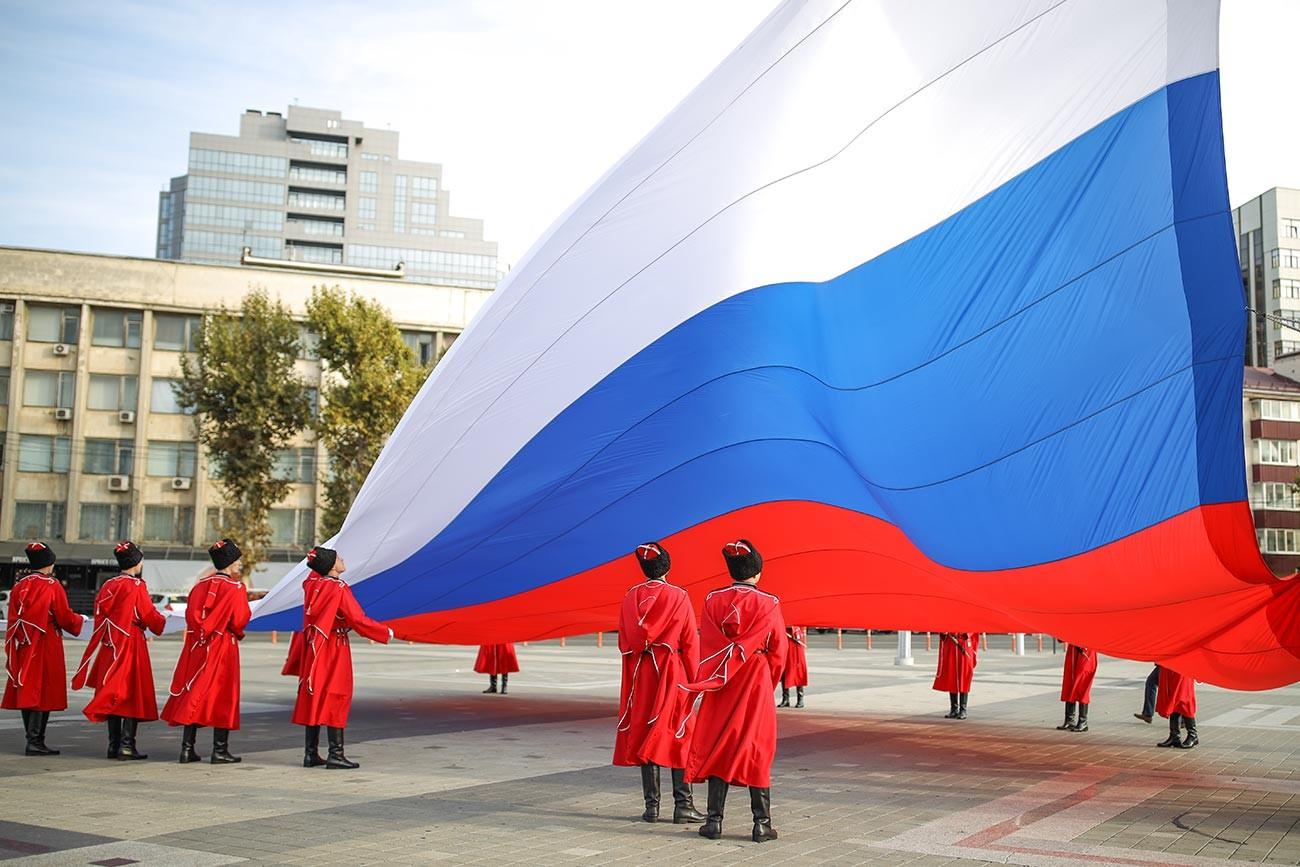 Торжественная церемония поднятия Государственного флага Российской Федерации казаками почётного караула Кубанского казачьего войска в День народного единства на главной городской площади в Краснодаре.