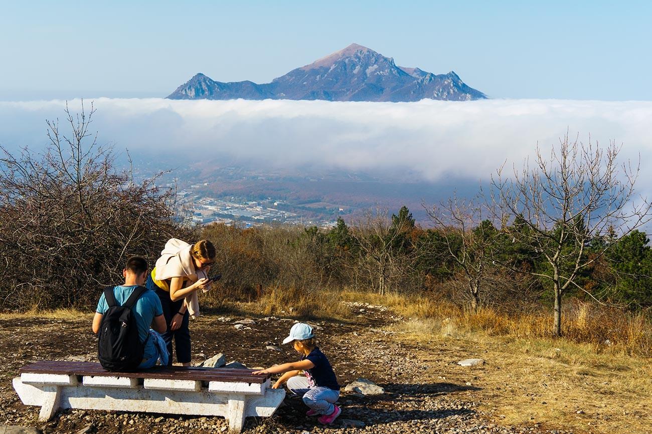Люди на смотровой площадке на вершине горы Машук с видом на гору Бештау в Пятигорске.