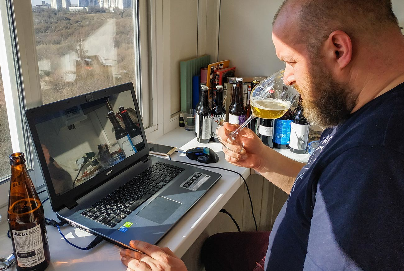 A beer chain consultant tastes some samples at home during a live video conference in Moscow during self-isolation.