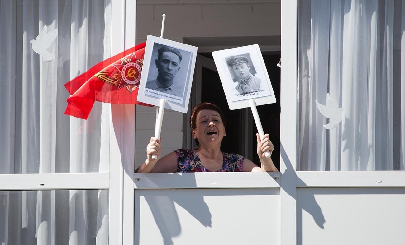 """Жителка на Тјумењ со портрети на ветерани на Втората светска војна пее песни од воените години со учесници во акцијата """"Парада дома""""."""