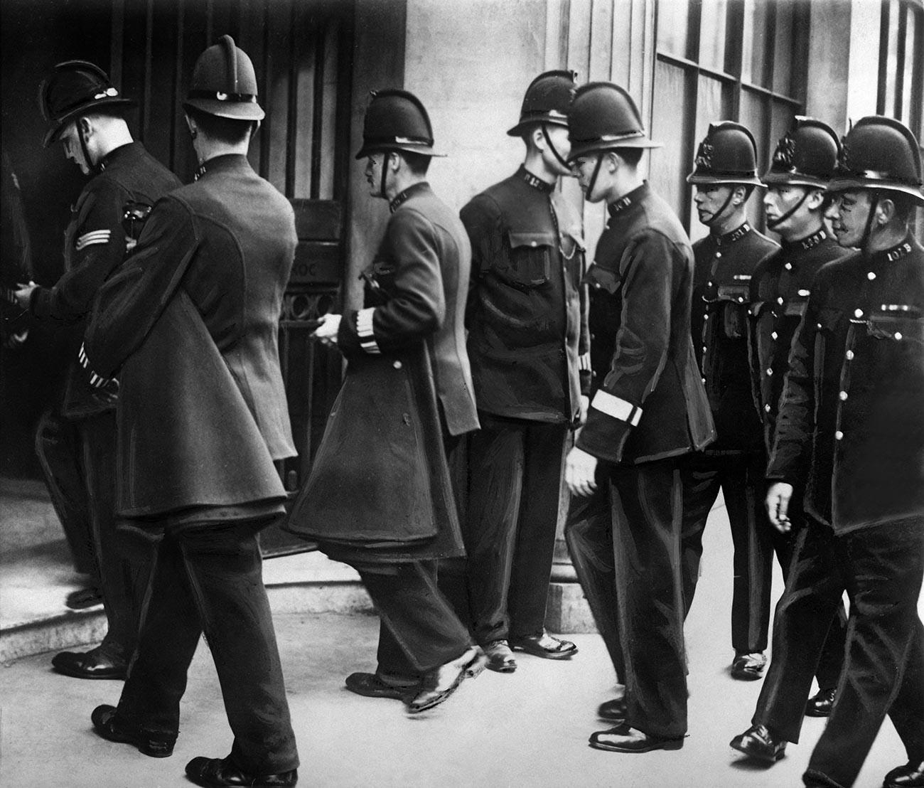 Policiers entrant à l'ARCOS, Londres