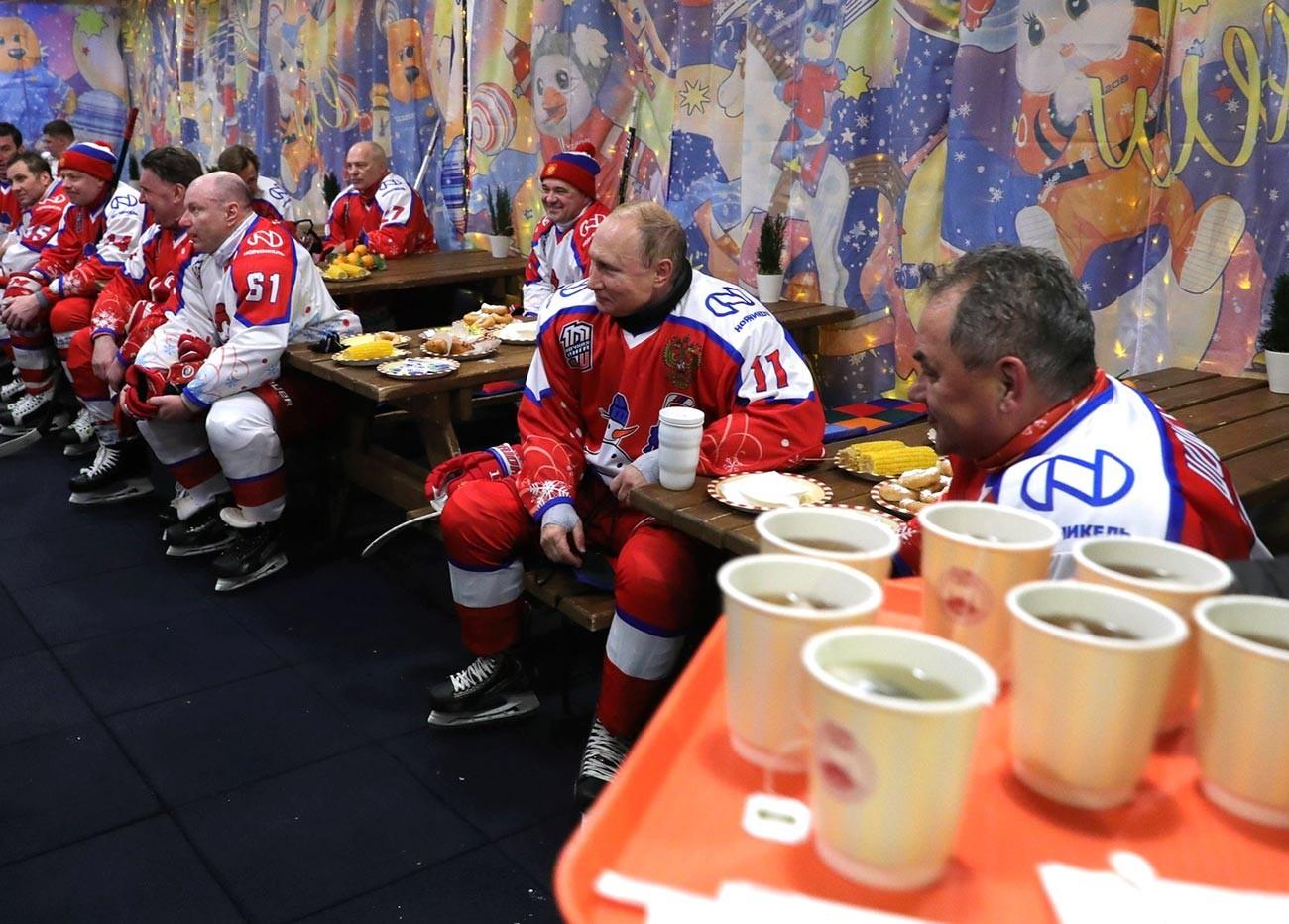 Vladimir Putin (kedua dari kanan) dan Menteri Pertahanan Rusia Sergei Shoigu (kanan) saat istirahat dalam pertandingan persahabatan malam tahun baru Liga hoki Malam di Lapangan Merah.