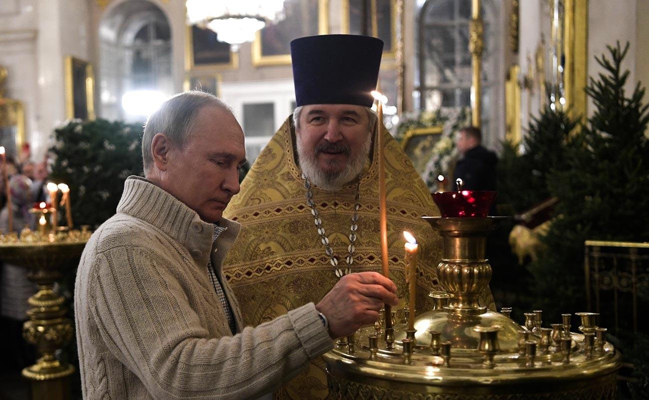 Vladimir Putin menghadiri kebaktian di Katedral Transfigurasi Sankt Peterburg bersama Kepala Katedral Nikolai Bryndinpada malam Natal.