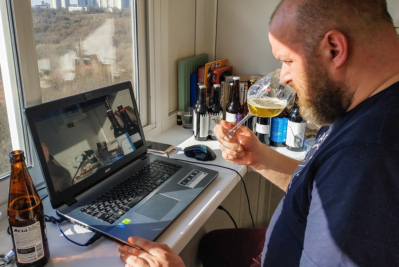 Un consultor de la cadena de cerveza prueba algunas muestras en casa durante una videoconferencia en vivo en Moscú durante el confinamiento.