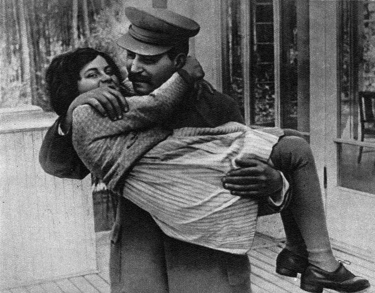 Joseph Stalin menggendong putrinya Svetlana dengan kedua tangannya.