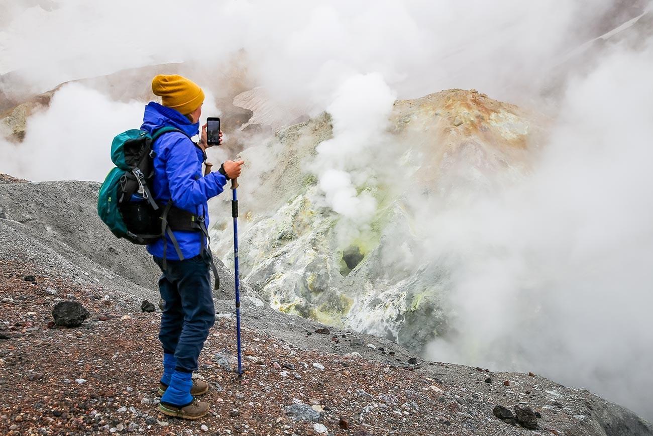 Turist na polju fumarol v kraterju vulkana Mutnovski.