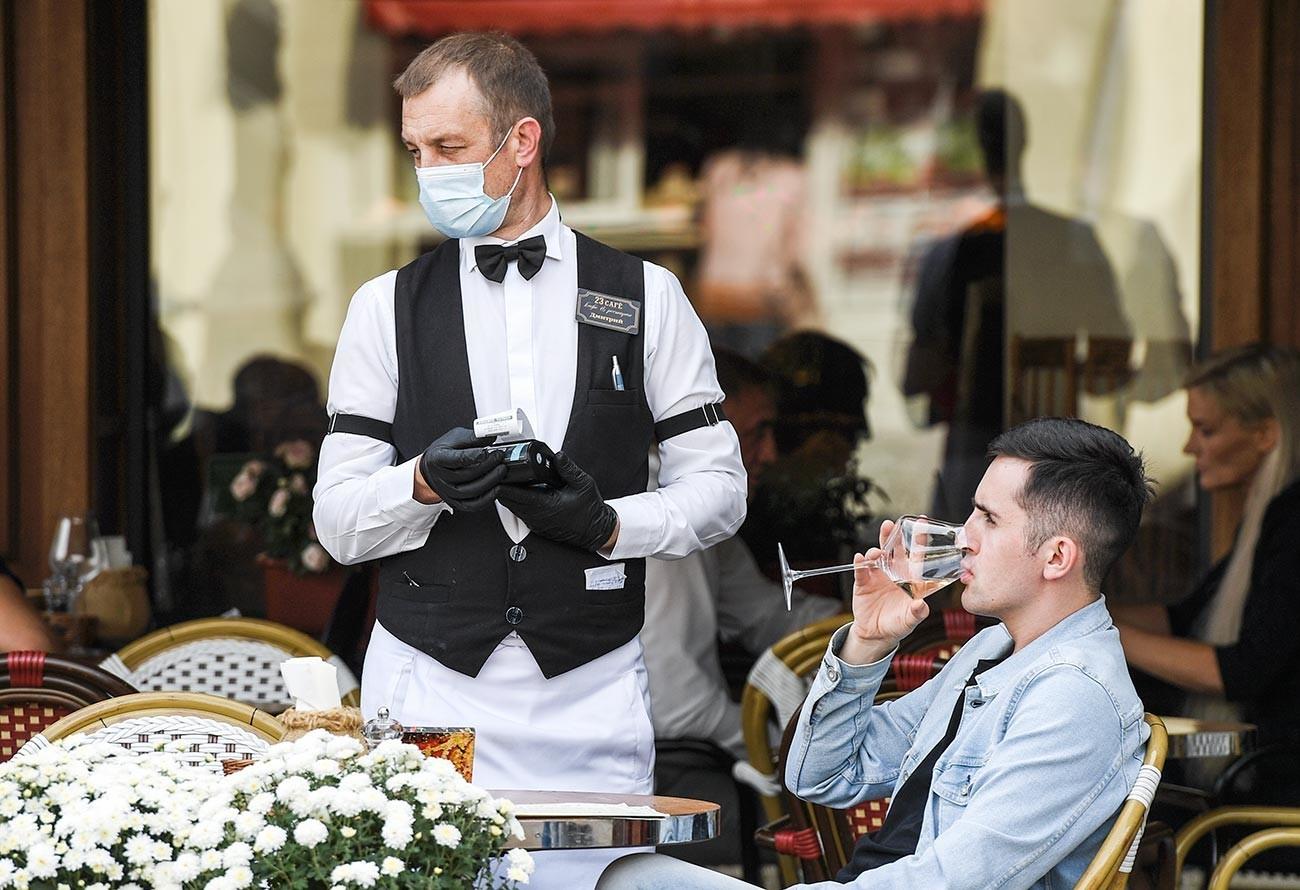 Natakar v zaščitni maski sprejema naročilo mladeniča v kavarni v Simferopolu.