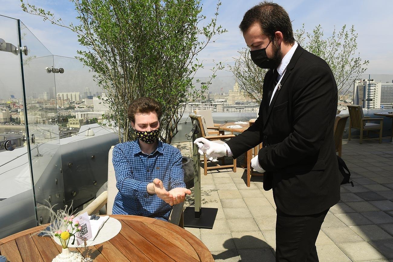 Zaposlen in obiskovalec, oba v zaščitnih maskah na novo odprti poletni terasi restavracije Sahalin v Moskvi.