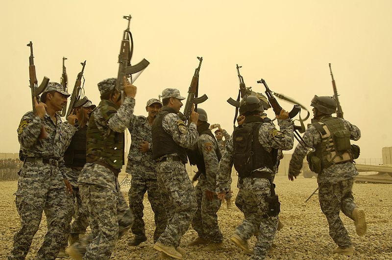 Policías iraquíes bailan portando sus AK-47