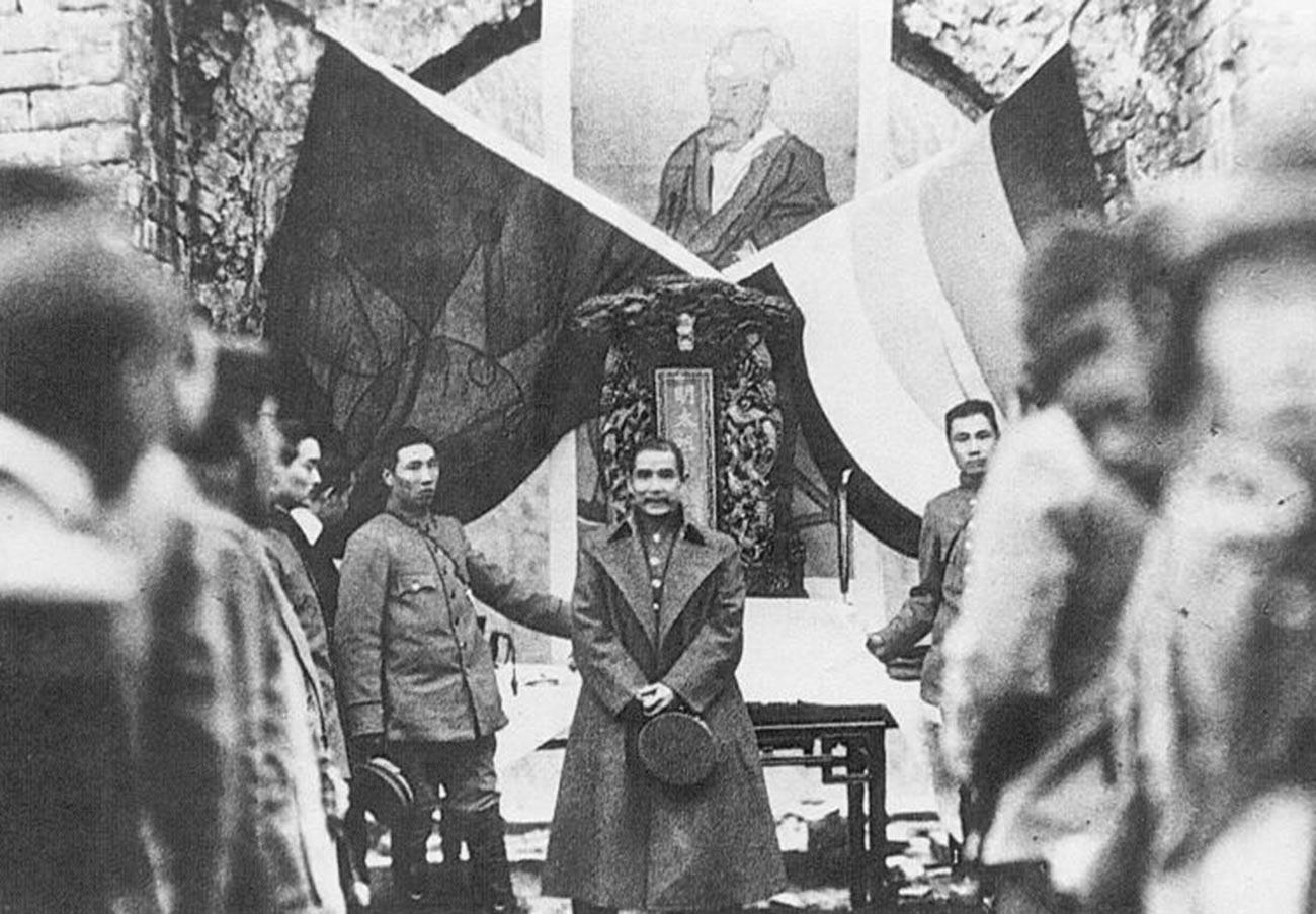 """Кинеска (Синхајска) револуција, 1912. г. Сун Јат Сен под заставама """"Пет раса у једној унији"""" и """"Плаво небо и бело сунце""""."""