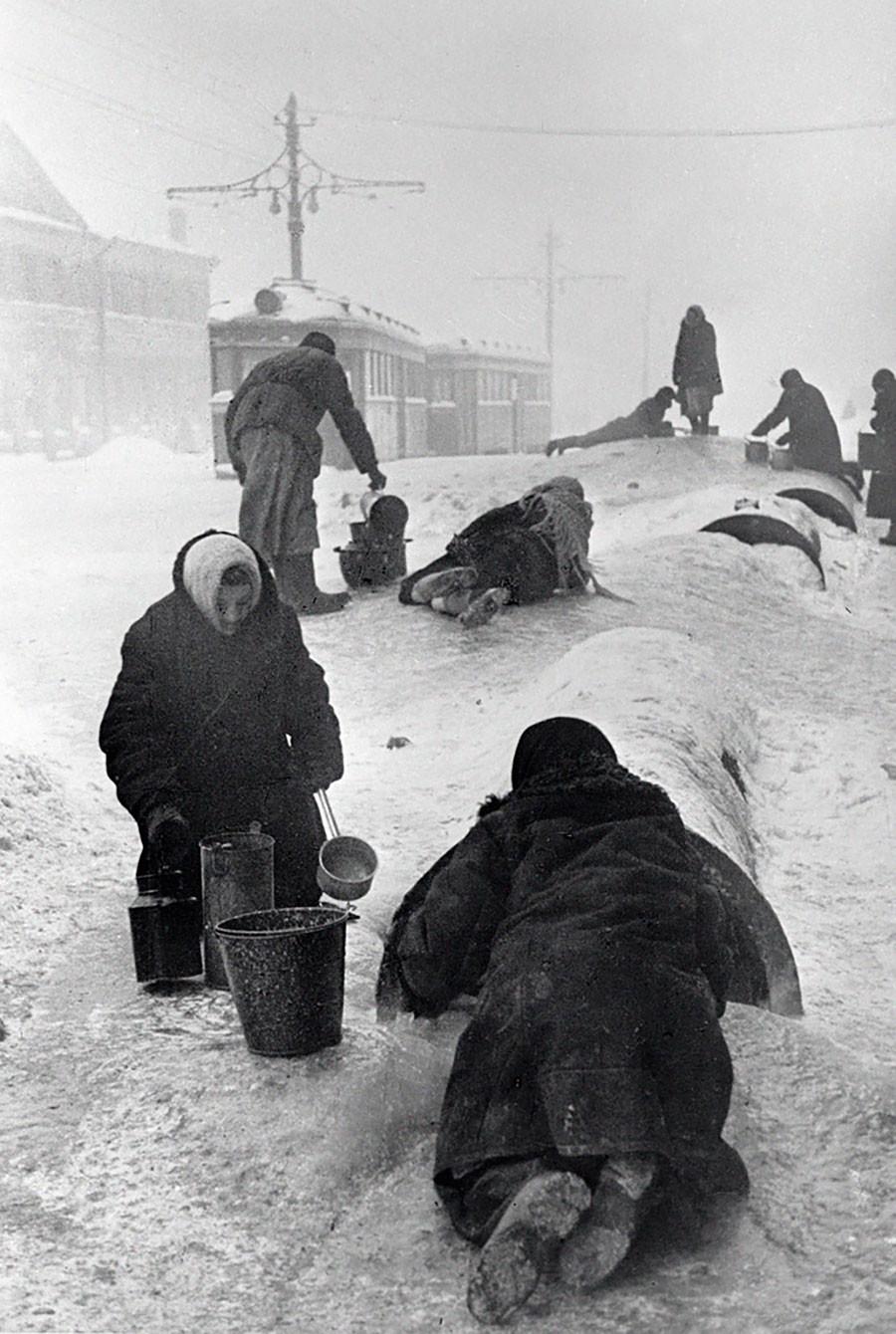 Les habitants de la ville de Leningrad remplissent leurs seaux depuis une conduite endommagée par une journée glaciale, janvier 1942.