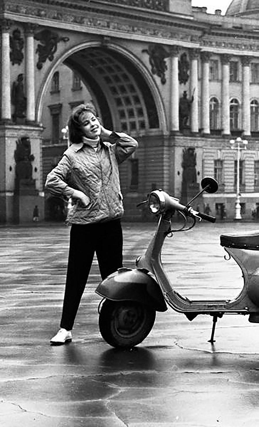 Un desfile de moda con una modelo femenina con el fondo del arco del Estado Mayor en Leningrado en los años 60.