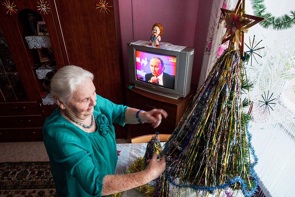 ОМСК, РУСИЯ - 23 ДЕКЕМВРИ 2016: Възрастна жена украсява коледно дърво, докато гледа на живо речта на Владимир Путин в дома за стари хора в Нежински.