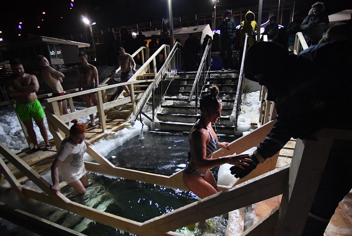 ウラジオストクで行列を作って水に飛び込む人々