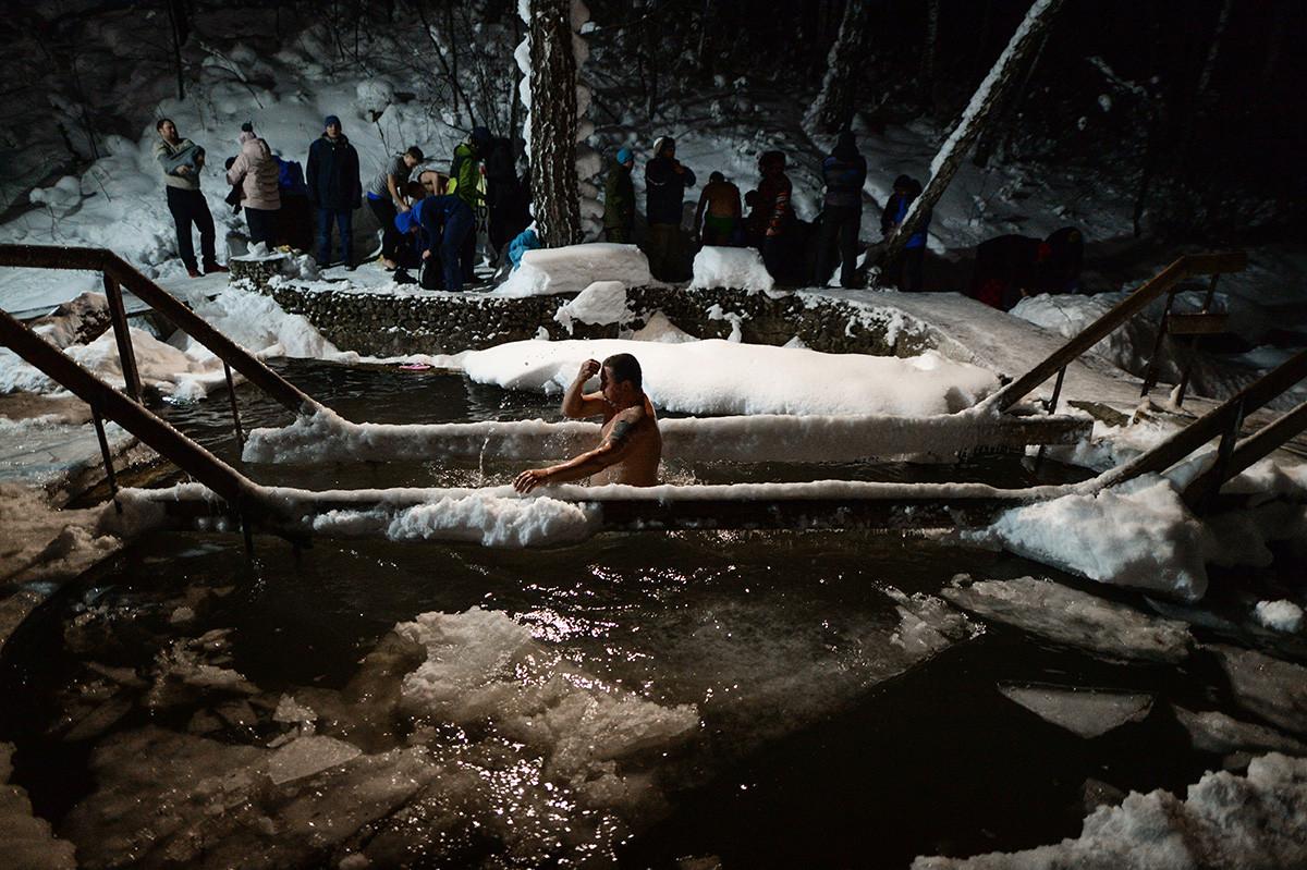 凍らない聖なる泉で水に浸かる人も