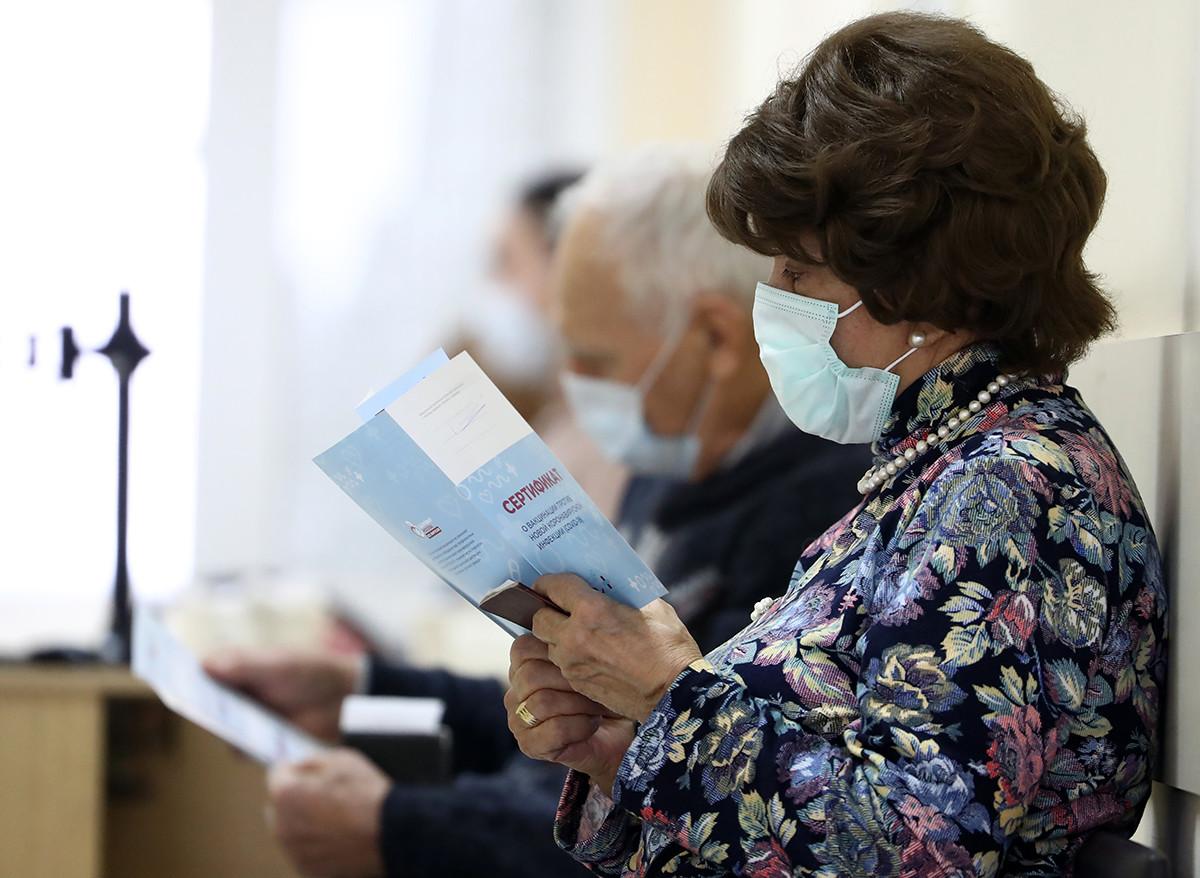 Orang-orang menunggu untuk menerima vaksin COVID-19 di pusat vaksinasi poliklinik diagnostik No.121, Moskow, Rusia, Kamis (14/1).