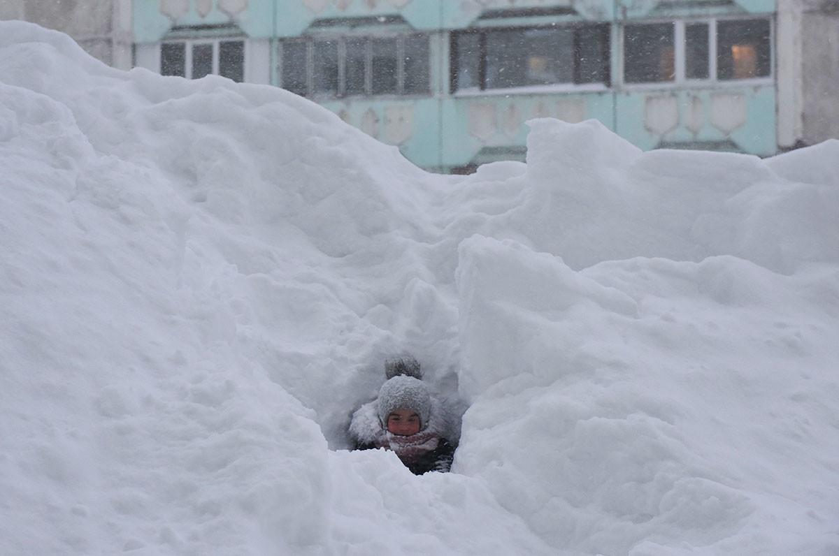 Criança brinca no pátio de edifício residencial em Norilsk