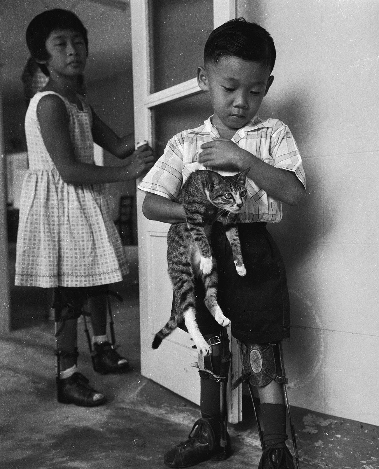 Fantek z mehansko napravo za pomoč pri hoji po preboleli otroški paralizi.