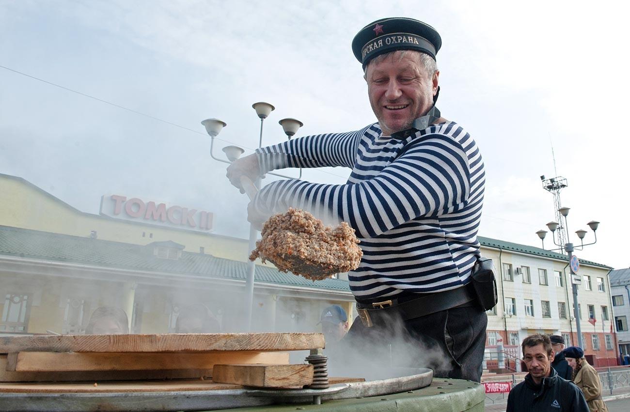 """Homens em reencenação histórica da Segunda Guerra Mundial comem """"gretchka""""."""