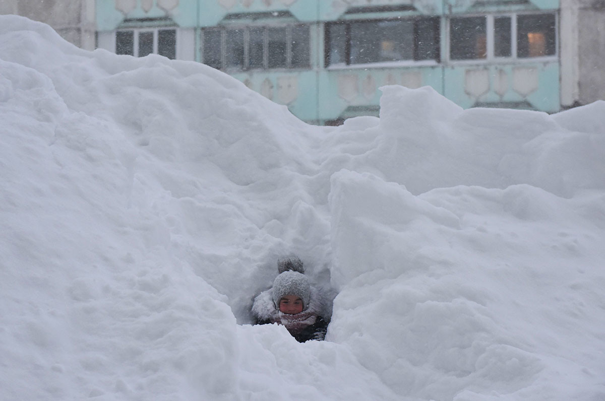 Дете играе в снежна преспа в двора на жилищна сграда в Норилск