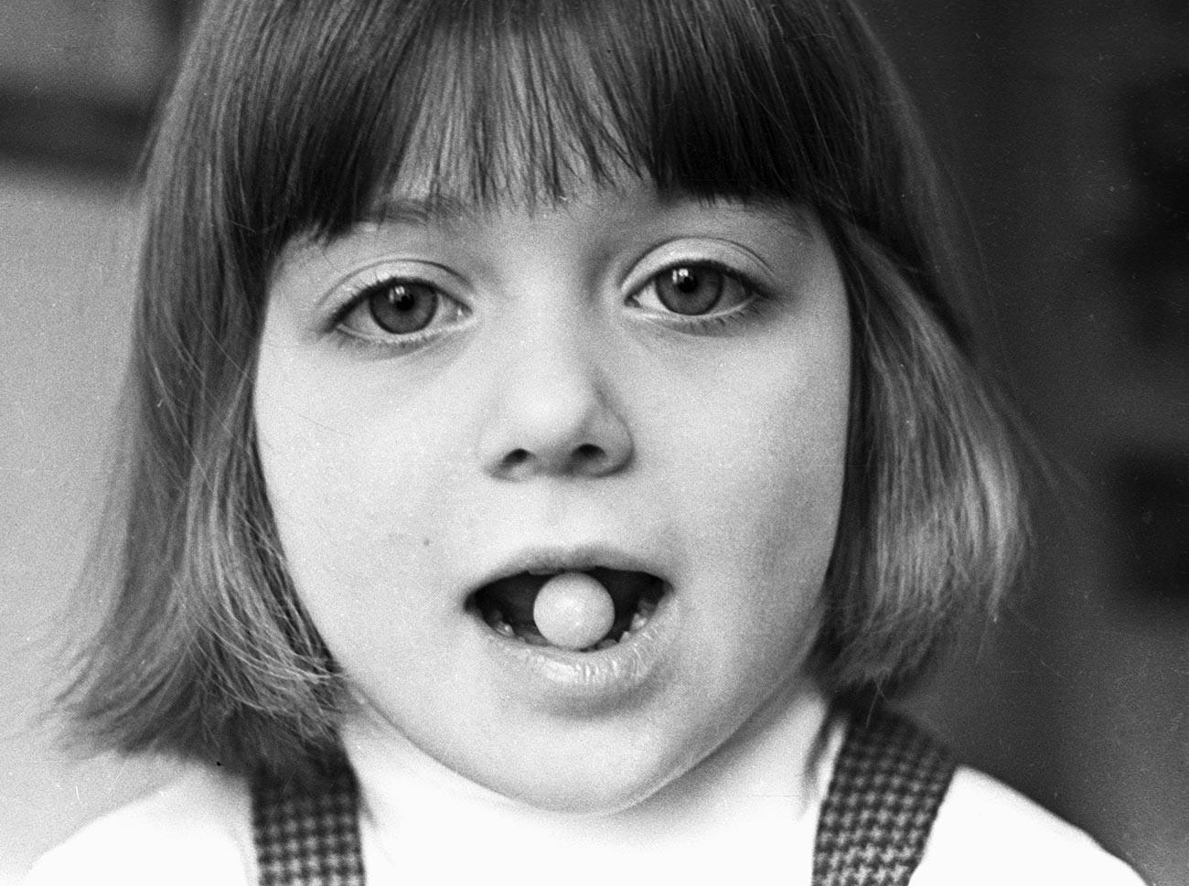 Menina segurando cápsula da vacina nos dentes no Instituto de Poliomielite e Infecções Encefálicas