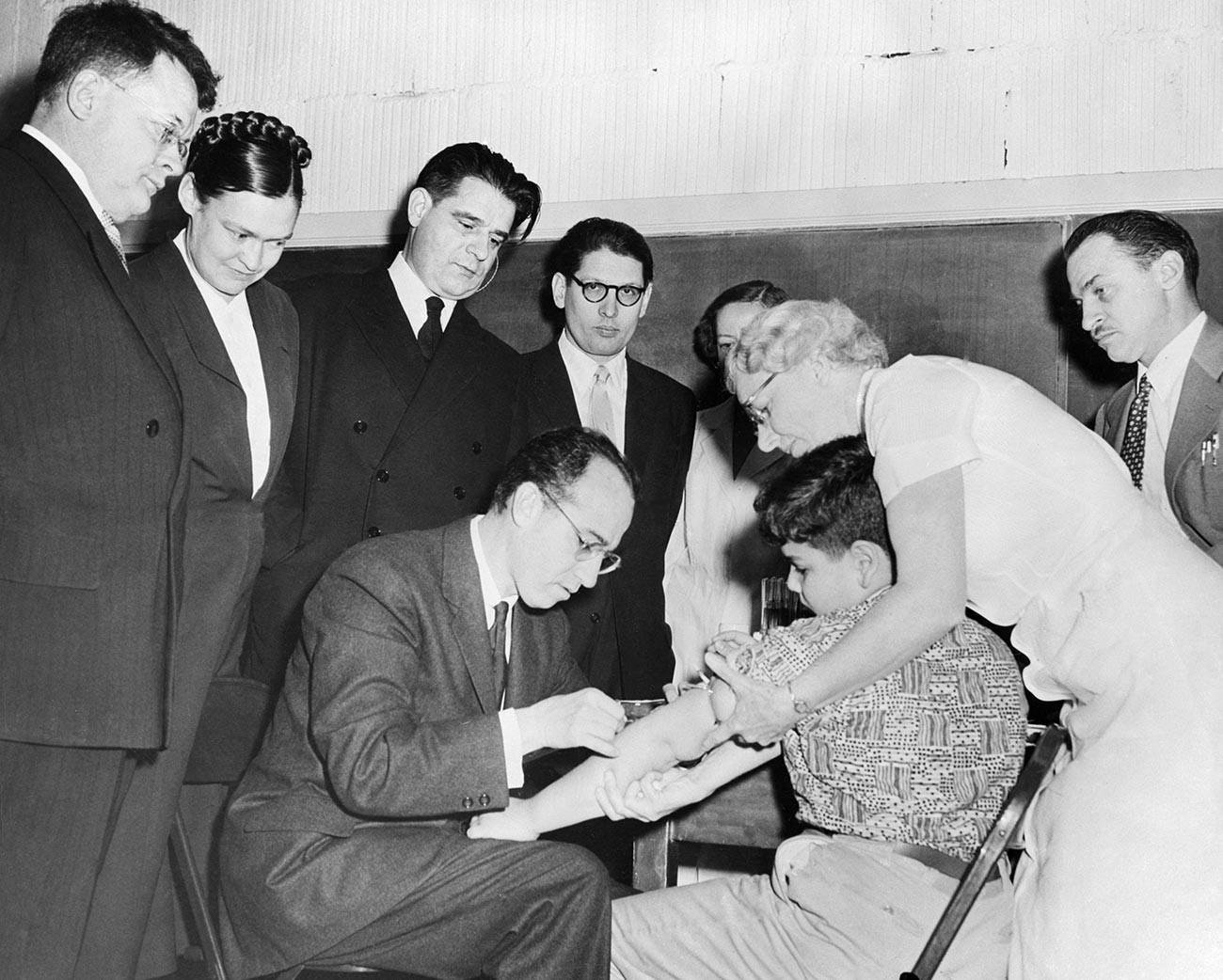 Cientistas russos em visita aos Estados Unidos observam Dr. Jonas Salk administrar injeção de sua vacina antipólio em Paul Anolik, de 9 anos