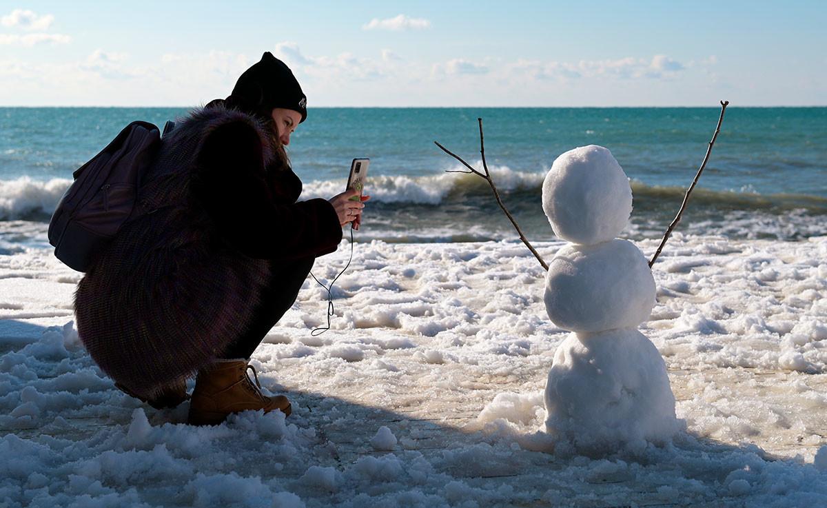 Девушка фотографирует снеговика на пляже в Адлерском районе в Сочи.