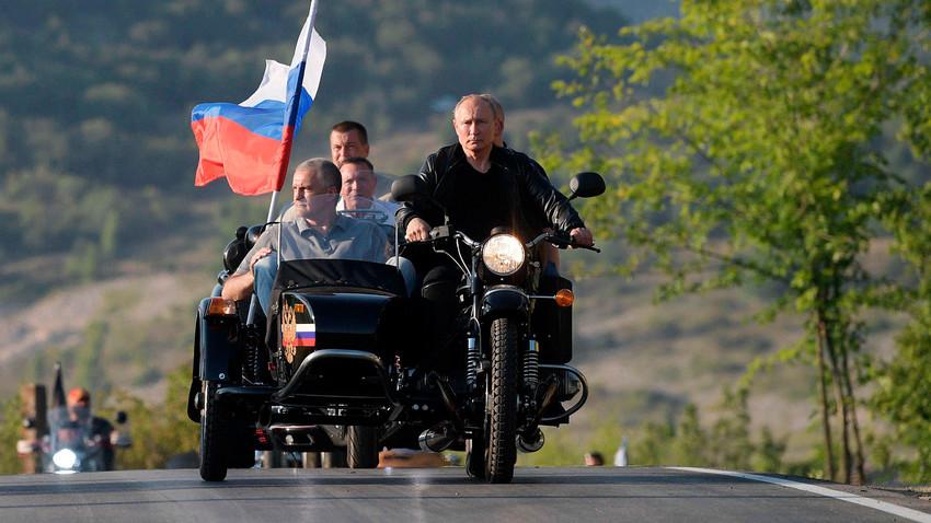 """Претседателот на Русија Владимир Путин на меѓународниот бајк-шоу """"Сенката на Вавилон"""" во организација на мотоклубот """"Ноќни волци"""" во Севастопољ зад воланот на мотоциклот """"Урал""""."""