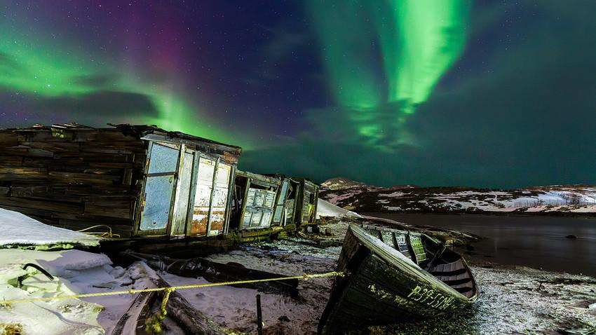 Cahaya Utara di atas kapal nelayan di Desa Teriberka, Murmanskaya oblast.