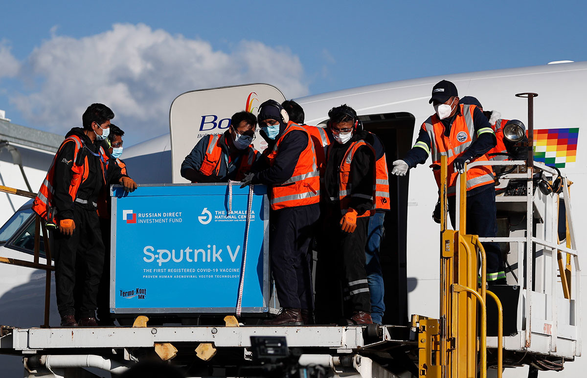Airport employees unload the first shipment of Russia's Sputnik V COVID-19 vaccine after it arrived at the international airport in El Alto, Bolivia, Jan. 28, 2021.