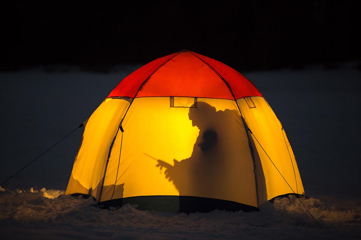 Seorang pria tengah memancing di es dari dalam tenda di Moskovskaya Oblast.