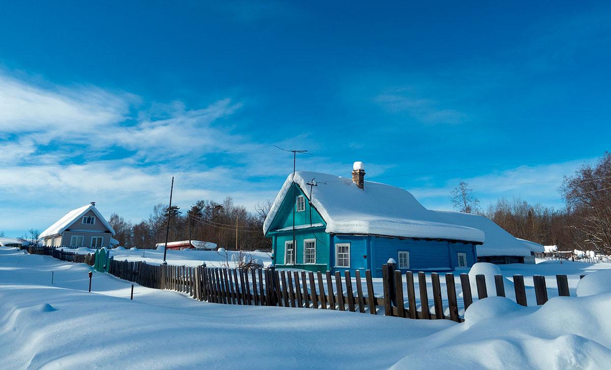 Holzhäuser im Schnee in dem karelischen Dorf Kokoila.