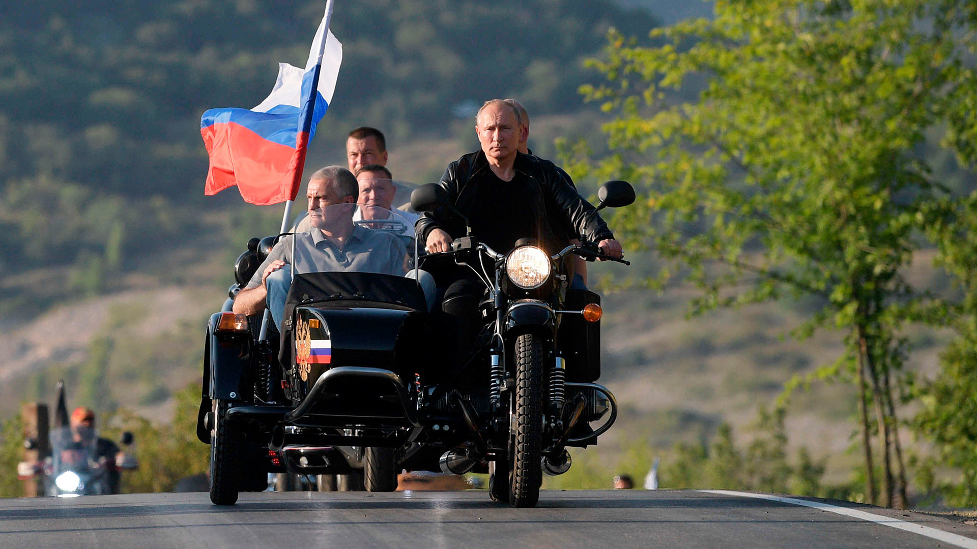 """August 10, 2019. Russian President Vladimir Putin participates in the international bike show in Sevastopol at the wheel of a motorcycle"""" Ural """" with a sidecar. On the left - the Head of the Republic of Crimea, Chairman of the Council of Ministers of the Republic of Kazakhstan Sergey Aksenov"""
