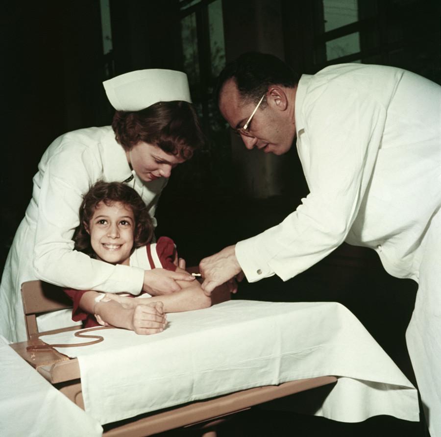 Jonas Salk et une infirmière administrent un vaccin antipoliomyélitique à une fillette américaine