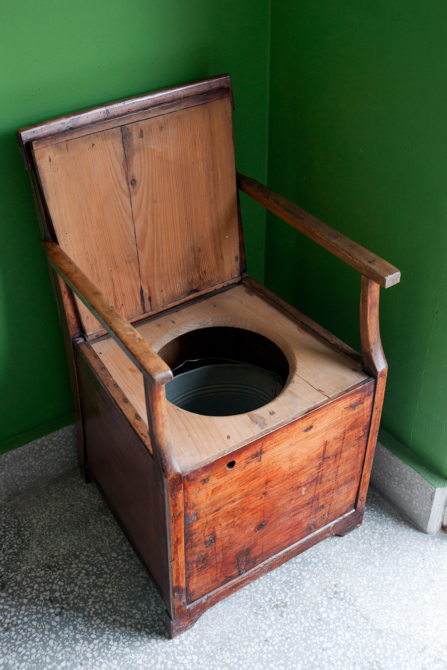 Vintage toilet made of wooden armchair and bucket.
