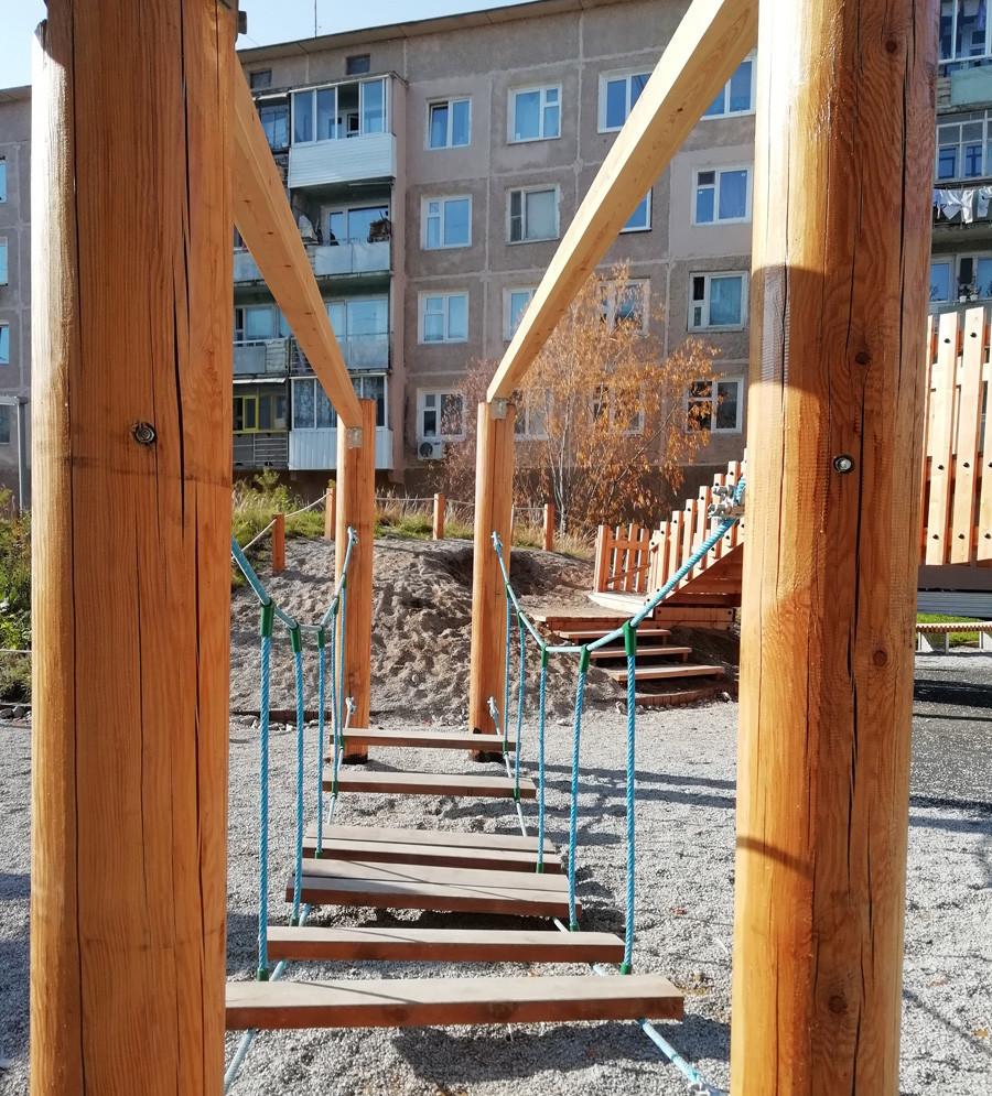 Taman bermain berbahan kayu di pekarangan permukiman.