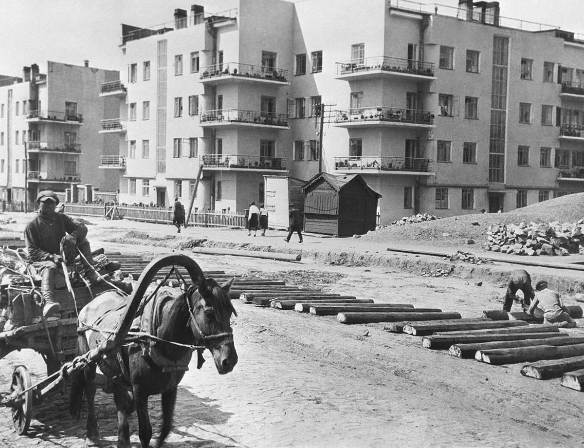 Novosibirsk, 1934 (circa). Operai durante la posa dei binari del tram vicino al complesso di edifici residenziali in via Chelyuskintsev, costruito nel 1933 come casa comune per le famiglie dei ferrovieri