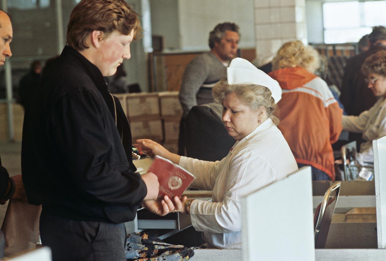 モスクワの食糧危機。モスクワのプロピスカのスタンプされたパスポートを提示している男性。