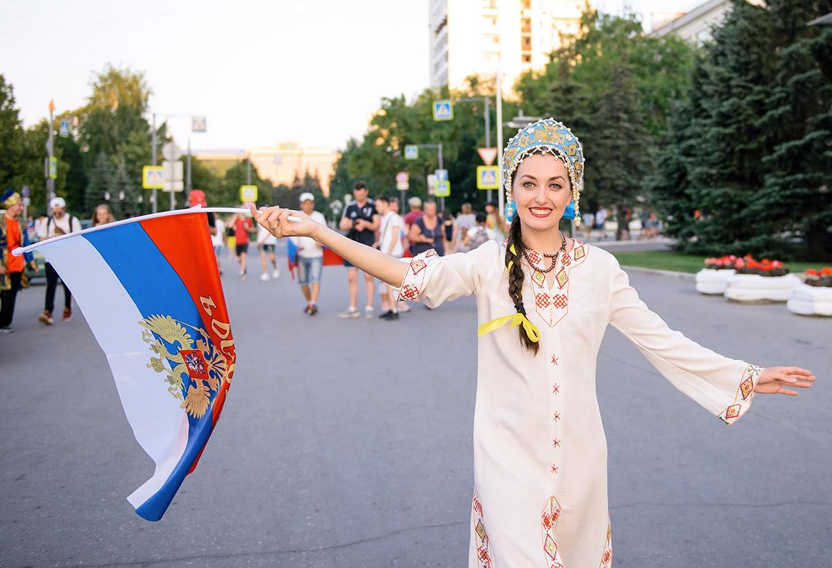 SAMARA, RUSIJA - 25. JUNIJ 2018: Ruska nogometna navijačica v tradicionalni ruski obleki z državno zastavo pred nogometno tekmo svetovnega pokala FIFA 2018 med Rusijo in Urugvajem.