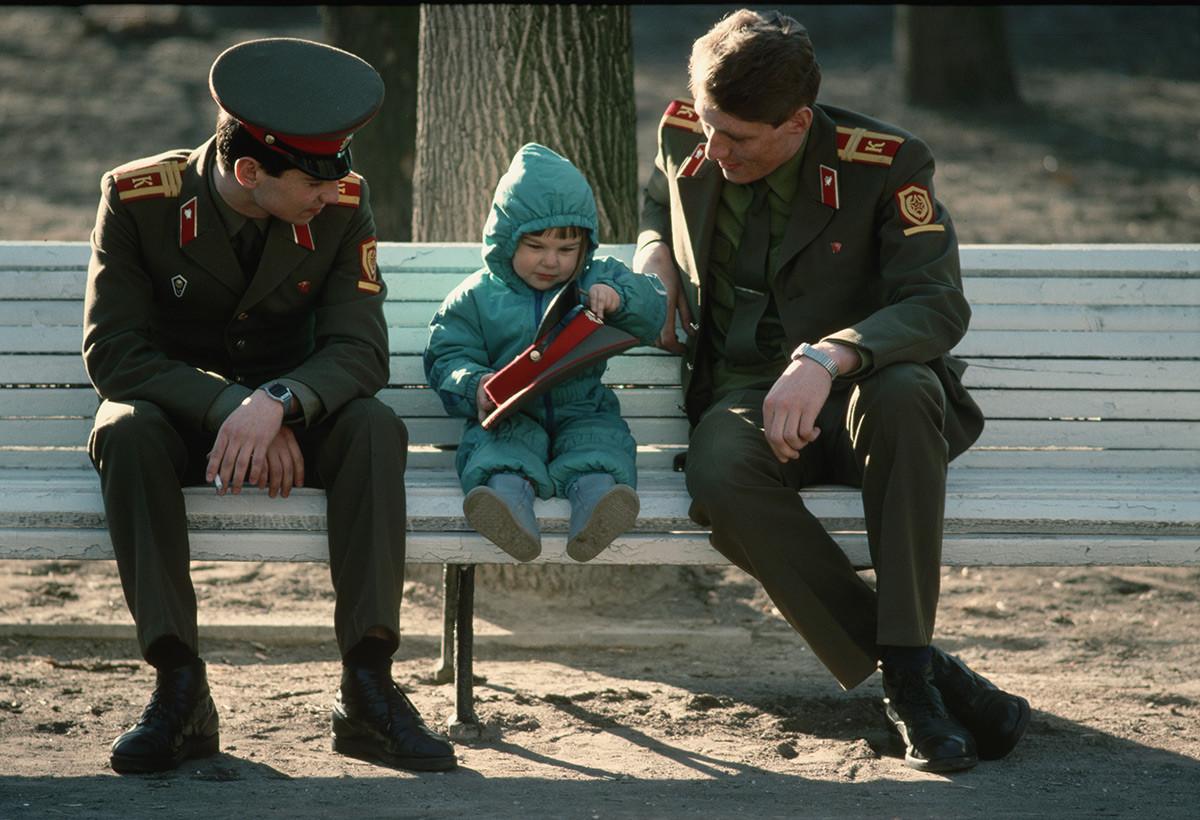 子どもとともに公園のベンチに座る兵士たち