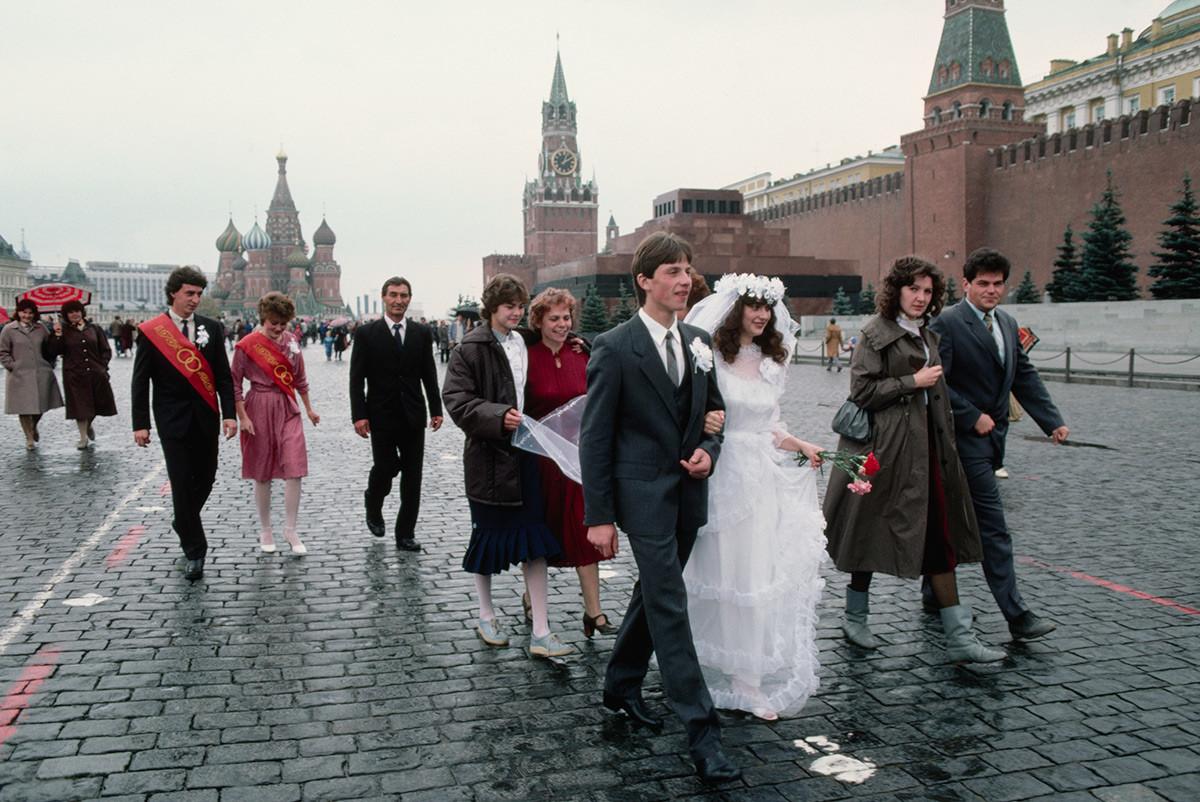 ソ連の伝統に従い、結婚式の日に写真撮影のために赤の広場に歩いて行く新郎新婦たち