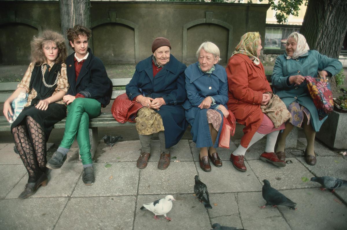 ベンチの上のジェネレーション・ギャップ。高齢女性たちと若いカップル
