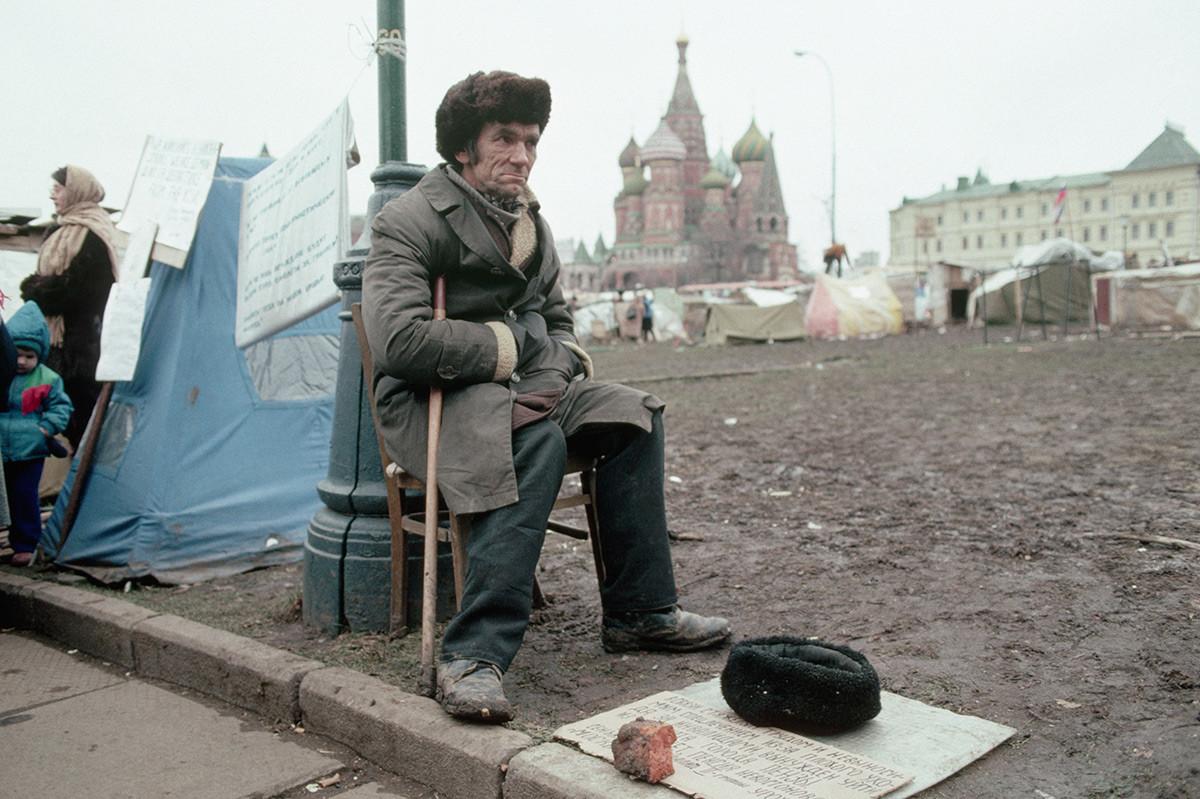 赤の広場近くの仮設テント村のそばに座るホームレス